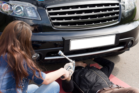 underneath: View over the shoulder of a female driver of a mechanic working on a roadside breakdown as she hands him his tools underneath the car Stock Photo