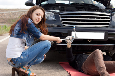 responded: Attractive trendy young woman fixing her car helping the mechanic who responded to her call for roadside assistance following a breakdown by handing him a socket spanner Stock Photo