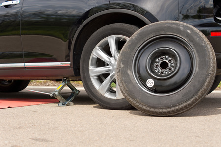 jacked: Changing the wheel on a car with the vehicle jacked up on a hydraulic jack and the spare wheel propped up against the front side of the car close up view