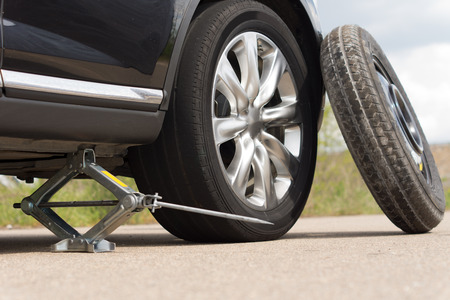 Jacking up a car to change a tyre after a roadside puncture with the hydraulic jack inserted under the bodywork raising the vehicle and the spare wheel balanced on the side 스톡 콘텐츠