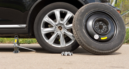 jacked: Fixing a puncture at the roadside with a view of the car jacked up with the spare tyre balanced against the side and nuts removed off the wheel