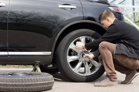 man nuts: Man changing his spare wheel replacing the original tyre with a fixed puncture tightening the nuts with a wheel spanner Stock Photo