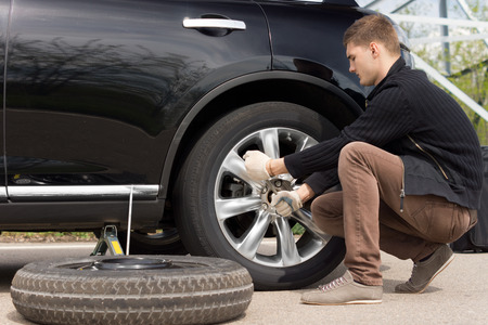 Mechanic changing a wheel during a roadside assistance call out to assist a driver in an emergency following a puncture Stock Photo