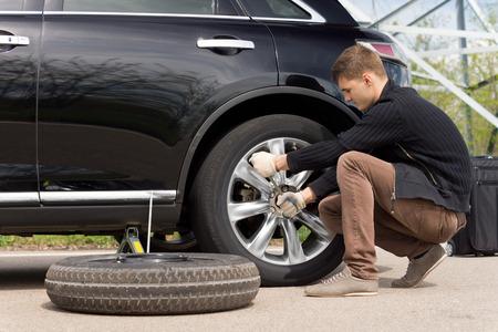 Молодой человек меняется к проколотой шине на своей машине, ослабив гайки колеса гаечным ключом до взвинчивают автомобиль