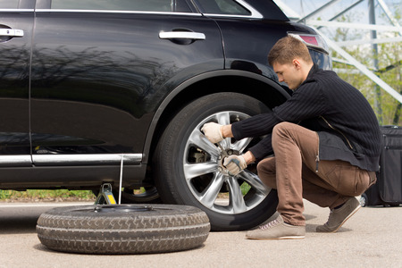 spare car: Young man changing the punctured tyre on his car loosening the nuts with a wheel spanner before jacking up the vehicle Stock Photo
