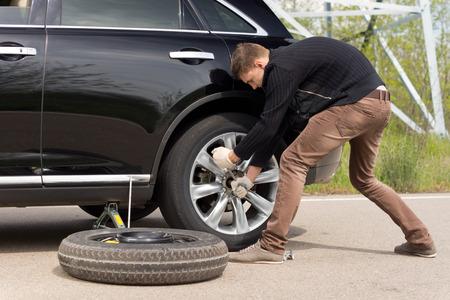 若い男が、ホイール レンチを努力の後ろの彼の重量を入れてハブ立ってのナットを緩めると戦い彼は彼の車のタイヤを変更するのに苦労