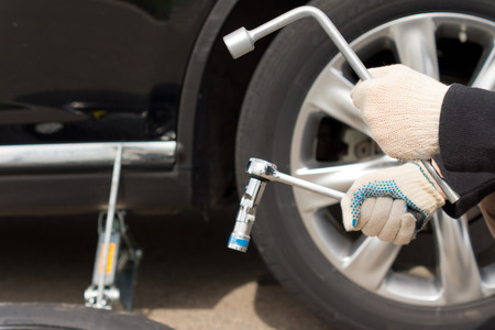 Closeup vie of the gloved hands of a man changing the tire on his vehicle following a puncture holding the wheel spanner and a socket wrench to loosen the nuts Stock Photo