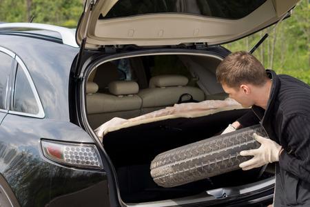 男性の国の道路上の穿刺の苦しみの後彼のハッチバック車オープン ブートから彼のスペアタイヤを削除します。 写真素材