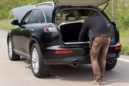 bonnet up: Man looking for tools in the boot of his hatchback car parked at the roadside with its bonnet up following a breakdown Stock Photo