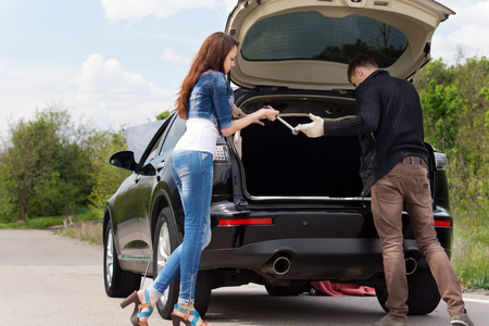 Young couple getting ready to change a tyre on their car which has broken down at the side of a rural road as the man passes a wheel spanner to his sexy young girlfriend photo
