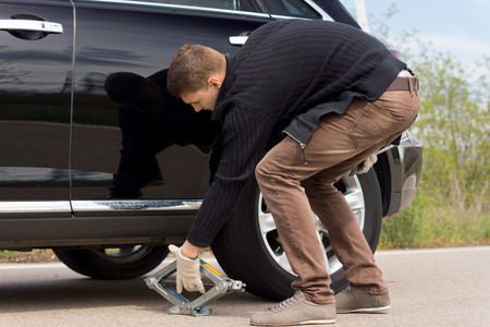 puncture: Man placing a hydraulic jack under his car to raise the vehicle allowing him to change the wheel for a spare following a roadside puncture Stock Photo