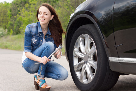 Smiling young woman getting ready to change a tyre crouching down at the side of the car holding a wheel spanner in her hands photo
