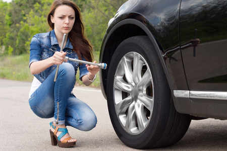 Confused woman looking at a wheel spanner with a puzzled expression as she kneels in the road alongside her car which has broken down photo
