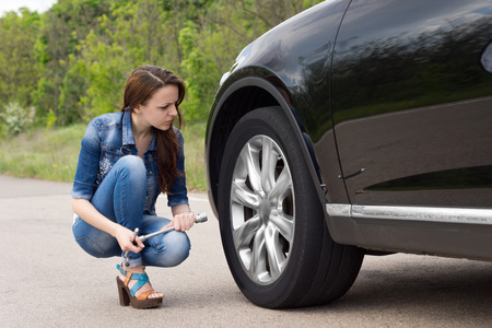 Attractive sexy slender young woman checking out a flat tyre on her car as she kneels in the road holding the wheel spanner photo