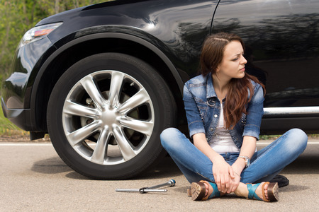 roadside assistance: Young woman waiting for roadside assistance for her car sitting cross legged in the road looking expectantly down the road with the wheel spanner lying alongside her