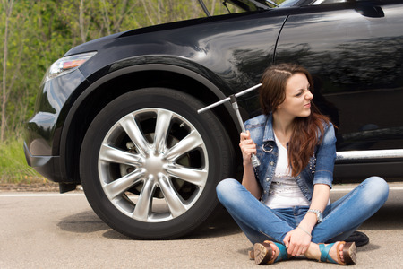 roadside assistance: Perplexed young woman waiting for roadside assistance after her car breaks down at the side of the road sitting holding the wheel spanner and grimacing