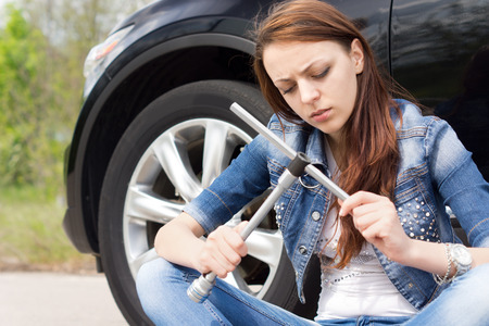 ignorant: Ignorant woman frowning at a wheel spanner as she sits on the road alongside her car following a breakdown waiting for assistance Stock Photo