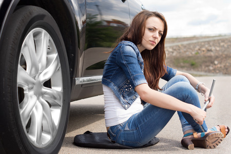 Female driver waiting for roadside assistance sitting on the road alongside her car with the wheel spanner in her hand with a bored expression photo