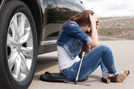 Distraught young woman waiting for roadside assistance sitting alongside her broken down car on a rural road with her head in her hands photo