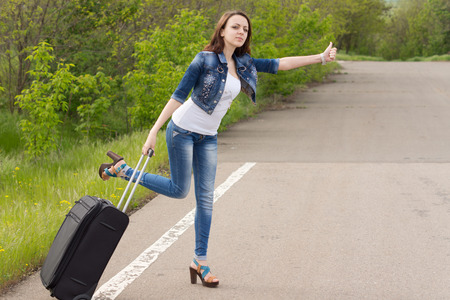 soliciting: Desperate sexy beautiful young woman trying to thumb a lift holding her suitcase in one hand while leaning out into the road trying to attract the attention of passing motorists Stock Photo