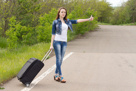 Young brunette attractive Caucasian woman wearing blue jeans, denim jacket, white T-shirt and high heels, holding a black trolley while hitchhiking, in a green area, in summer photo
