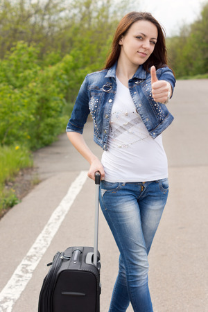 Smiling attractive young woman giving a thumbs up as she stands at the side of a rural road with her suitcase trying to thumb a lift photo