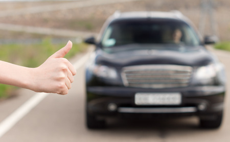 Woman hitchhiking soliciting a ride holding her hand out into the road in a thumbs up gesture to draw the attention of an approaching motorist photo