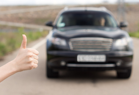 Woman giving a thumbs up gesture as she stands at the side of a rural road after a breakdown hitchhiking trying to stop passing traffic, focus to her hand photo