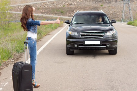Woman hitchhiking after a breakdown with her car standing at the side of the road with her luggage gesturing at a passing motorist with her hand trying to get him to pull over photo