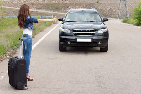 Young woman hitchhiking with a suitcase on a rural road flagging down an approaching car with her thumb as she solicits a lift photo