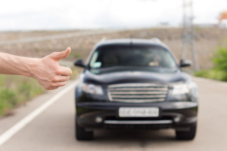 soliciting: Close up of the hand of a young man standing thumbing a lift at the roadside trying to catch the attention of a female driver in an approaching car