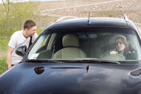 persuade: Young man chatting up a female driver talking to her through the passenger window as he tries to persuade her to give him a lift