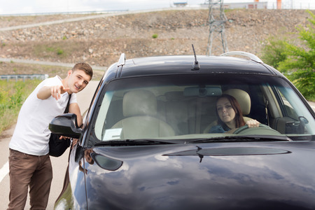 Female driver asking a handsome young for directions as he stands at the roadside pointing out the route for her on a rural road