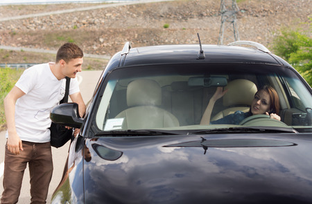 persuade: Young male hitchhiker looking for a lift talking to a female driver through the passenger window of her car as he tries to persuade her to give him a ride