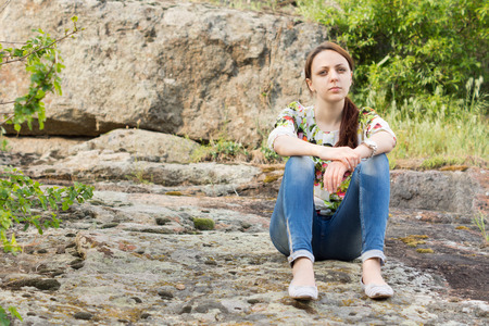 meditative: Lonely beautiful young woman with a serious expression sitting on rocks in the mountains enjoying a moment of peace and solitude