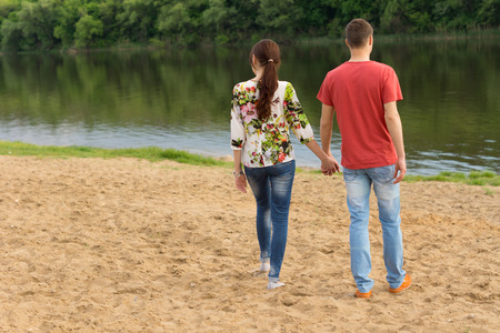 holding hands while walking: Rear view of a young romantic couple wearing blue jeans and holding hands while walking towards the edge of a lake with ripples and reflections of the green foliage, in a warm summer day