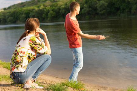 courting: Young man skimming stones across the water of a tranquil mountain lake watched by his young girlfriend sitting in the sunshine on her haunches Stock Photo