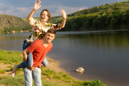 Young woman having a fun piggy back ride on her boyfriends back waving with both hands at the camera and laughing as they play together alongside a scenic mountain lake photo