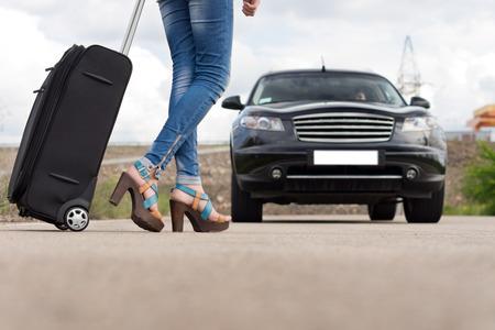 tight jeans: Faible angle des pieds d'une femme portant des jeans serr�s bleu et talons hauts tout en portant un trolley noir vers une voiture classique noir sur la route