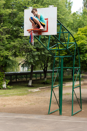 Young teenage girl fixing a basketball net sitting crouched on the hoop on the goalpost as she threads it round the metal hoop photo