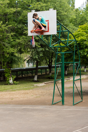 Agile young teenage girl repairing a basketball net balancing precariously on the metal hoop against the backboard on the goalpost as she threads it around the hoop photo