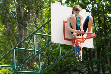 Agile young girl fixing a net on a basketball goal post sitting on top of the metal hoop attaching it with her hands photo