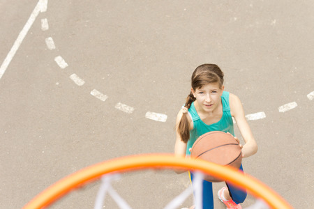 Young teenage athlete playing basketball standing below the goal taking aim as she prepares to shoot and throw the ball photo