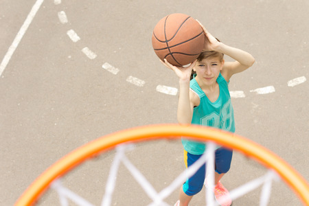 Young girl taking aim at the goal on a basketball court standing with the ball raised aiming at the hoop, view from above photo