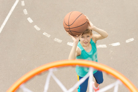 Teenage girl playing basketball taking aim at the goal with the ball raised in her hands, view from on top of the goalpost and net photo