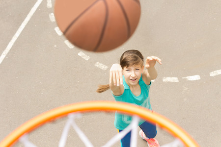 outdoor basketball court: Attractive young teenage girl shooting a basketball at the hoop as she practises her aim and shooting a goal
