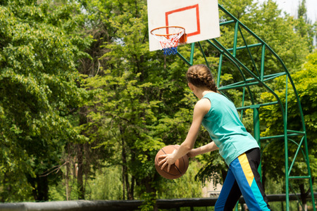 goalpost: Sporty slender teenage girl playing basketball holding the ball in her hands as she moves forwards eyeing the goalpost on an outdoor court against green trees