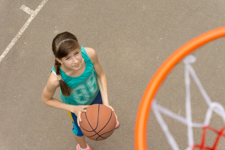 Attractive young teenage girl on a basketball court viewed from above holding the ball in her hands watching and waiting photo