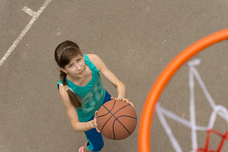 Teenage girl playing a game of basketball about to throw the ball at the goal and net pictured from above the goalpost photo