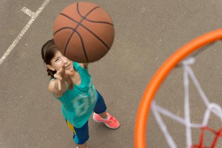 Vista desde la parte superior del aro y la red de una joven adolescente de tiro a canasta en baloncesto Foto de archivo